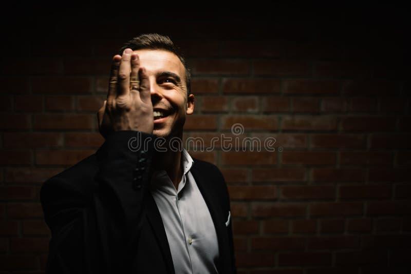 El hombre de moda en un fondo del negro lleva a cabo su mano en la cara imágenes de archivo libres de regalías