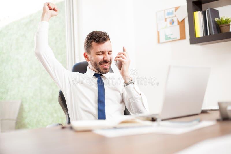 El hombre de negocios acaba de conseguir a un nuevo cliente sobre el teléfono foto de archivo libre de regalías