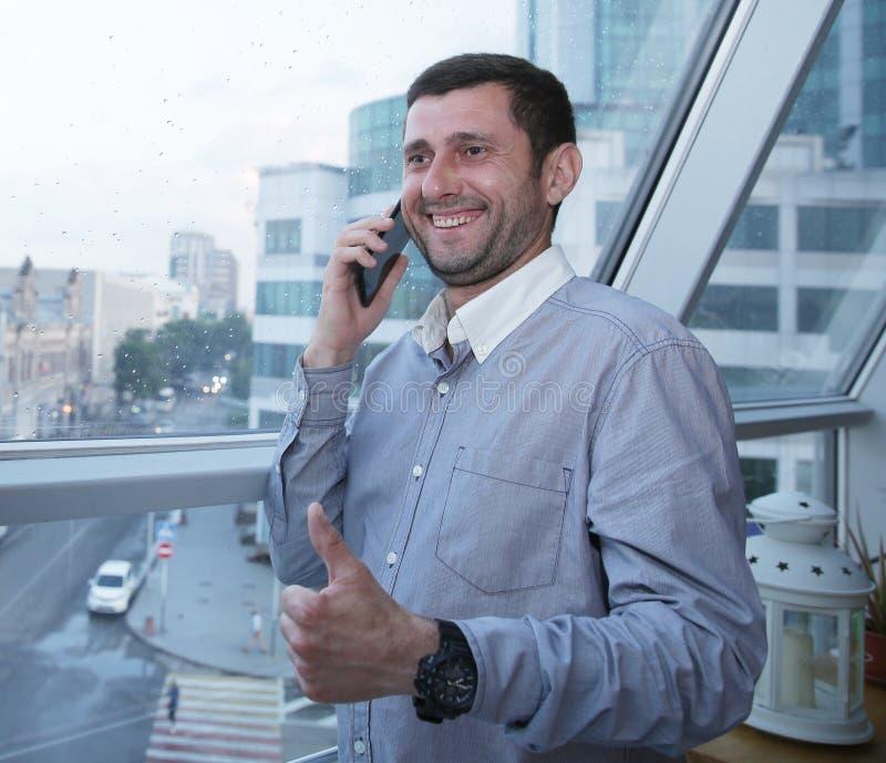 El hombre de negocios acertado con una sonrisa en su cara que habla en un teléfono móvil detiene su pulgar contra la perspectiva  imagen de archivo libre de regalías