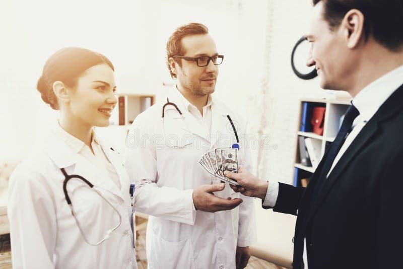 El hombre de negocios acertado da el dinero a un doctor que ha curado enfermedad Concepto de la corrupción del ` s de la medicina imágenes de archivo libres de regalías