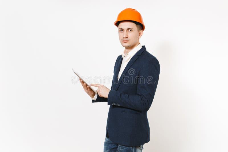 El hombre de negocios acertado hermoso joven en traje oscuro, ordenador protector de la PC de la tableta de la tenencia del casco foto de archivo libre de regalías