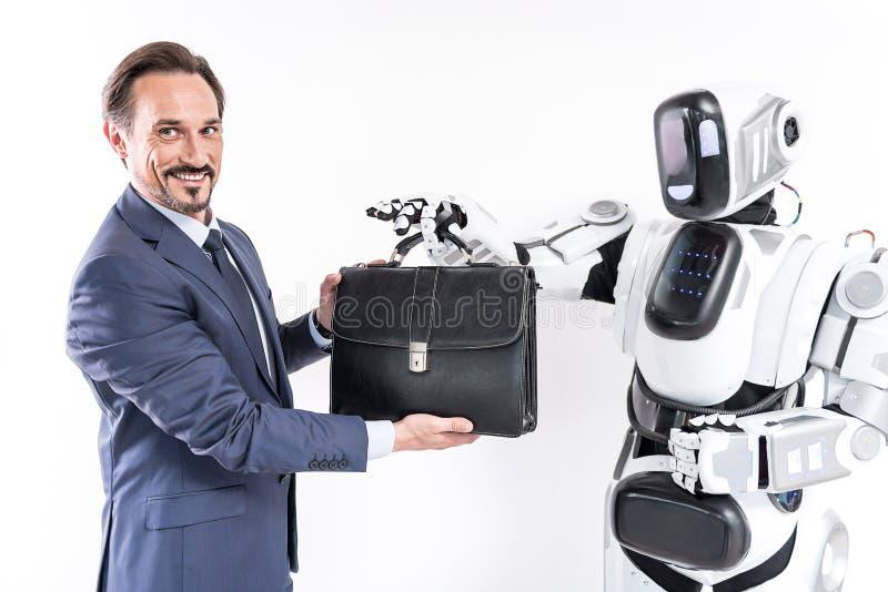 El hombre de negocios adulto feliz se está colocando con el robot y está llevando a cabo la cartera fotos de archivo libres de regalías