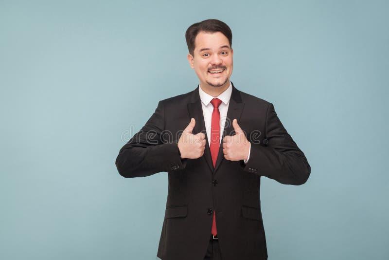 El hombre de negocios adulto joven atractivo demuestra los pulgares para arriba como s fotografía de archivo libre de regalías