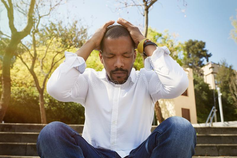 El hombre de negocios africano americano joven en ropa informal puso sus manos en su cabeza y tomar una respiración profunda afue foto de archivo