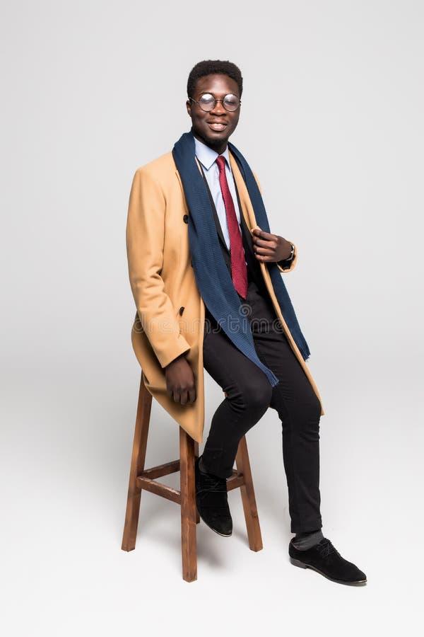 El hombre de negocios afroamericano amistoso en capa en silla aisló el fondo blanco foto de archivo libre de regalías