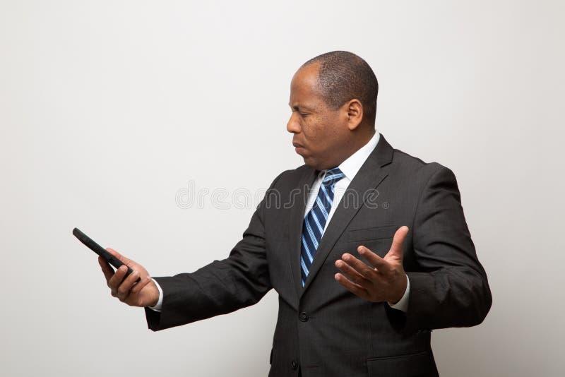 El hombre de negocios afroamericano confundido utiliza el teléfono elegante en Gray Background ligero fotos de archivo