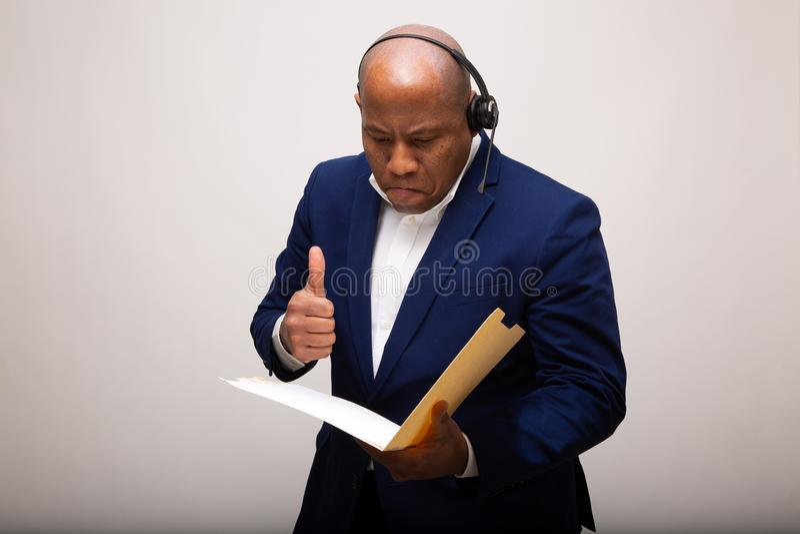 El hombre de negocios afroamericano mira la carpeta con los pulgares para arriba imagen de archivo libre de regalías