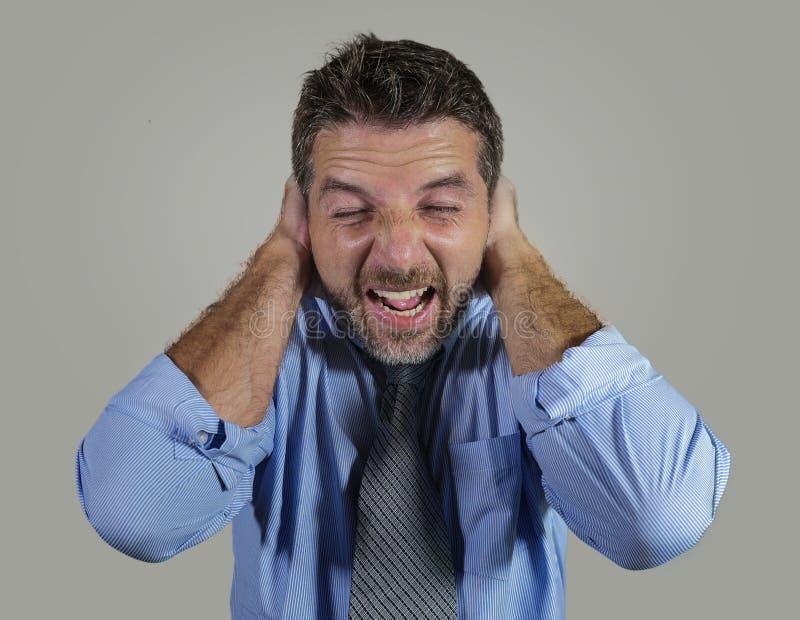 El hombre de negocios agotado y subrayado atractivo en la sensaci?n del dolor de cabeza del sufrimiento de la camisa y de la corb imágenes de archivo libres de regalías
