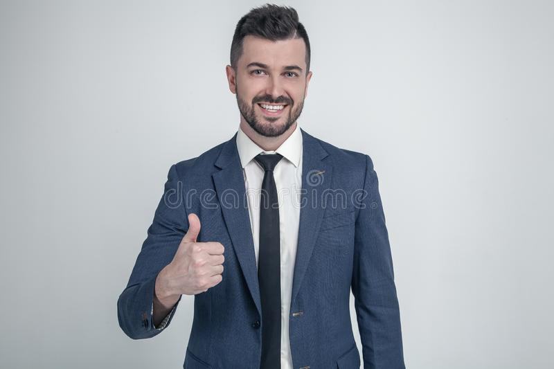 El hombre de negocios alegre manosea con los dedos encima de la presentaci?n y de la sonrisa en la c?mara vestido en un traje clá imagen de archivo