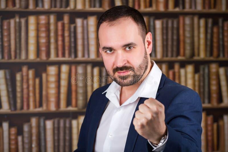 El hombre de negocios amenaza con un puño en la biblioteca imagen de archivo