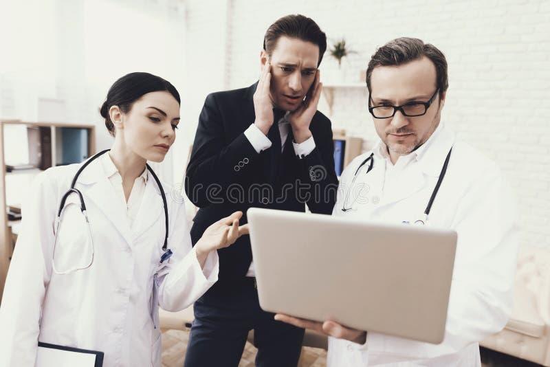 El hombre de negocios ansioso mira la pantalla del ordenador portátil en manos del doctor Examen médico imágenes de archivo libres de regalías