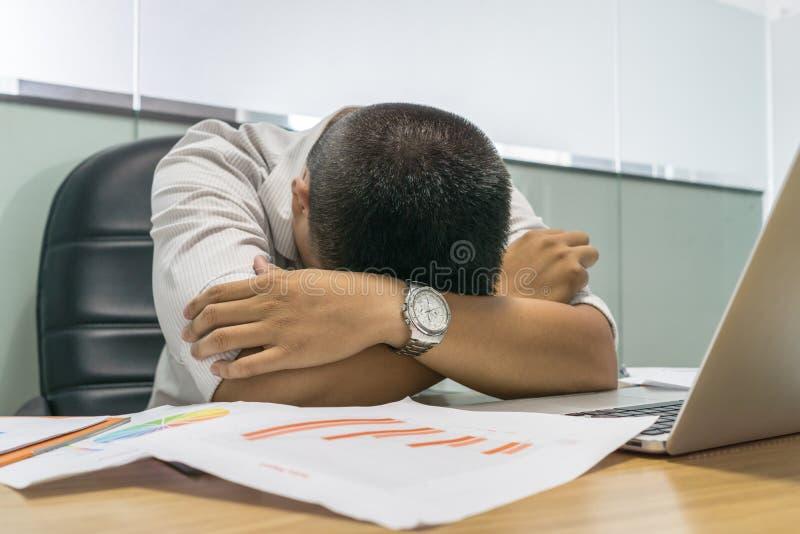El hombre de negocios asiático cansado se cae dormido delante del ordenador portátil imagen de archivo
