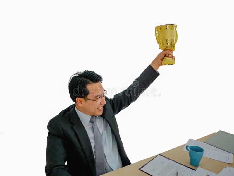 El hombre de negocios asiático consigue el trofeo de oro en fondo aislado imagen de archivo