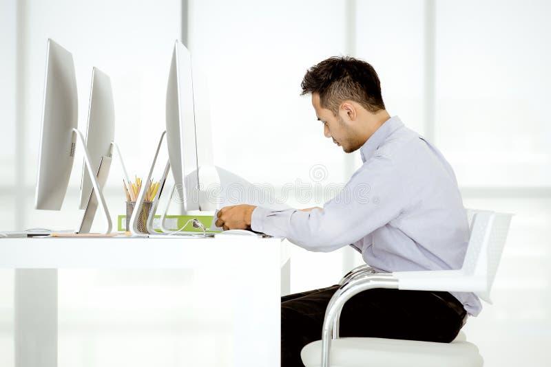 El hombre de negocios asiático joven en un casual está sentando el concentrado e i fotos de archivo libres de regalías
