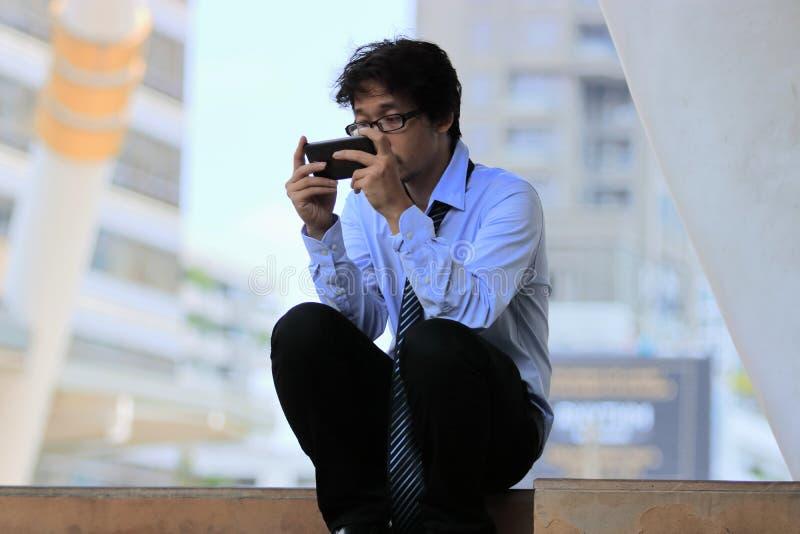 El hombre de negocios asiático joven parado usando el teléfono elegante móvil encuentra un trabajo Concepto deprimido del negocio fotografía de archivo