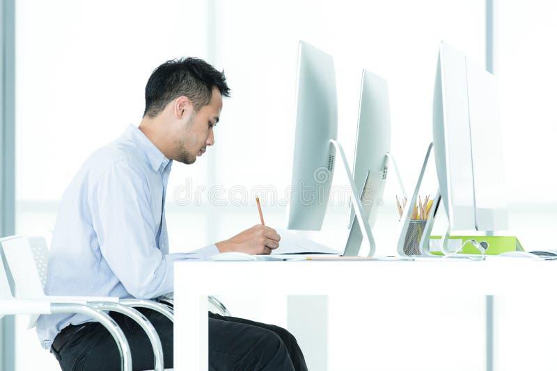 El hombre de negocios asiático joven que se sienta por el escritorio es trabajo y resto encendido foto de archivo