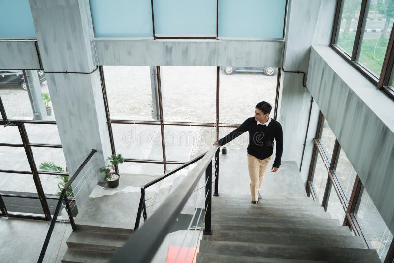 El hombre de negocios asiático que camina para arriba en las escaleras va a su sitio en arriba imagenes de archivo