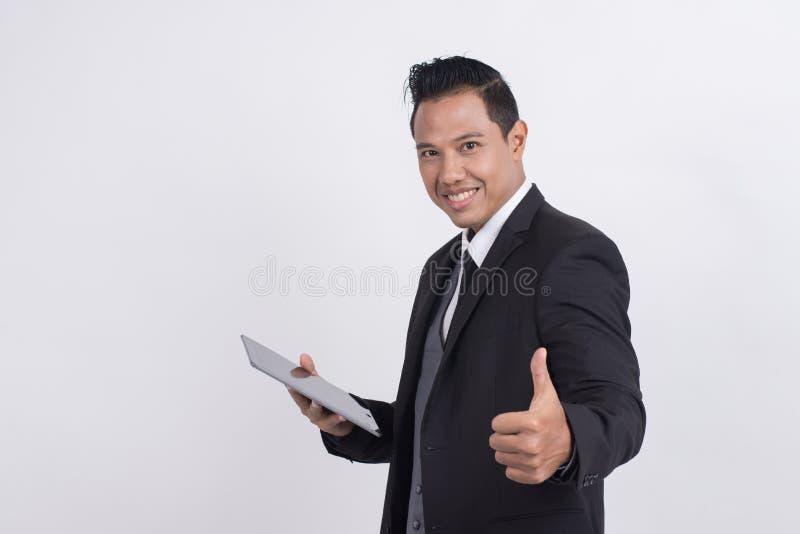 El hombre de negocios asiático sonriente feliz con los pulgares sube el gesto que mira la cámara imágenes de archivo libres de regalías