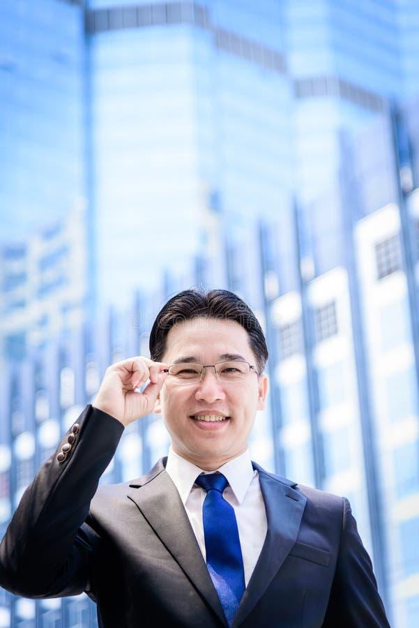 El hombre de negocios asiático tiene pensamiento en la visión con el edificio y c imagenes de archivo