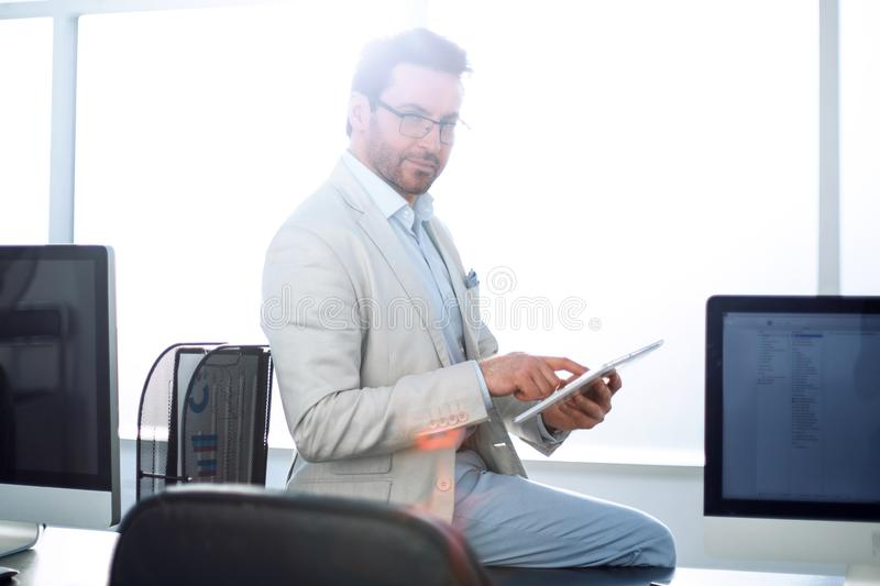 El hombre de negocios atento utiliza una tableta digital en una oficina moderna imágenes de archivo libres de regalías