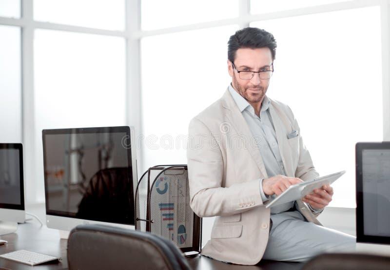 El hombre de negocios atento utiliza una tableta digital en una oficina moderna fotografía de archivo libre de regalías