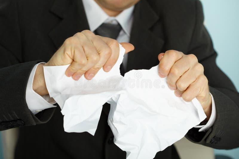 El hombre de negocios atormentó violentamente un papel foto de archivo libre de regalías