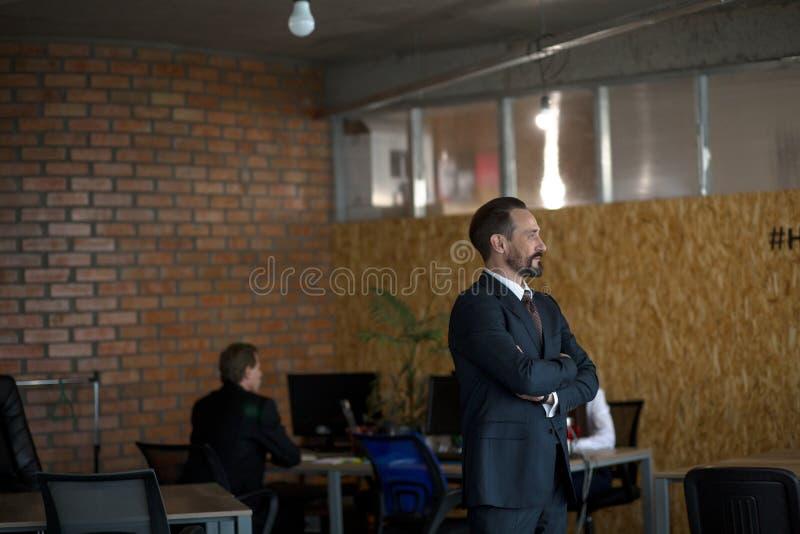 El hombre de negocios atractivo en traje trasero se está colocando en perfil en su oficina con los brazos cruzados Dos colegas es fotografía de archivo libre de regalías