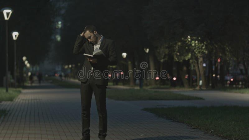 El hombre de negocios barbudo adulto que habla en el teléfono celular mientras que se coloca en la calle de la ciudad, hombre de  imágenes de archivo libres de regalías