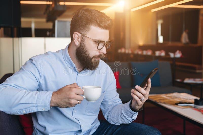 El hombre de negocios barbudo atractivo serio joven en camisa y vidrios azules se sienta en el sofá en café, bebe el café y aplic fotos de archivo