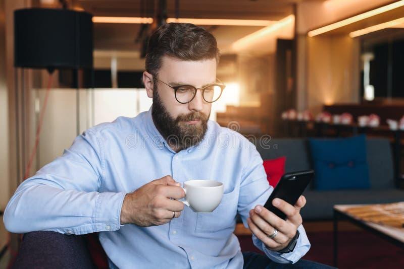El hombre de negocios barbudo atractivo serio joven en camisa y vidrios azules se sienta en el sofá en sitio, bebe el café y apli foto de archivo libre de regalías