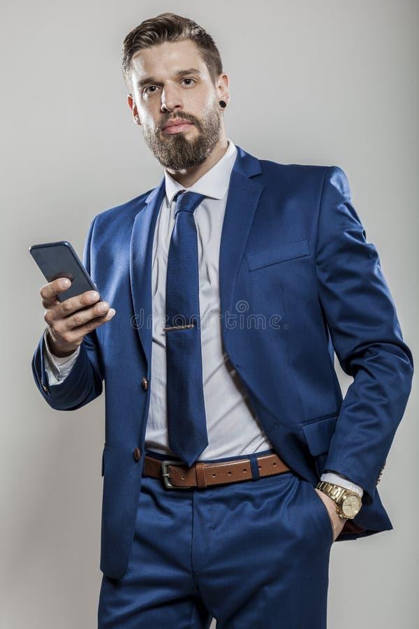 El hombre de negocios barbudo en traje azul act?a el tel?fono elegante fotos de archivo