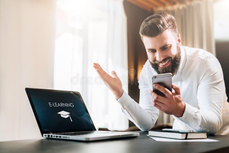 El hombre de negocios barbudo en una camisa blanca se está sentando en una tabla delante de un ordenador portátil con un aprendiz foto de archivo libre de regalías