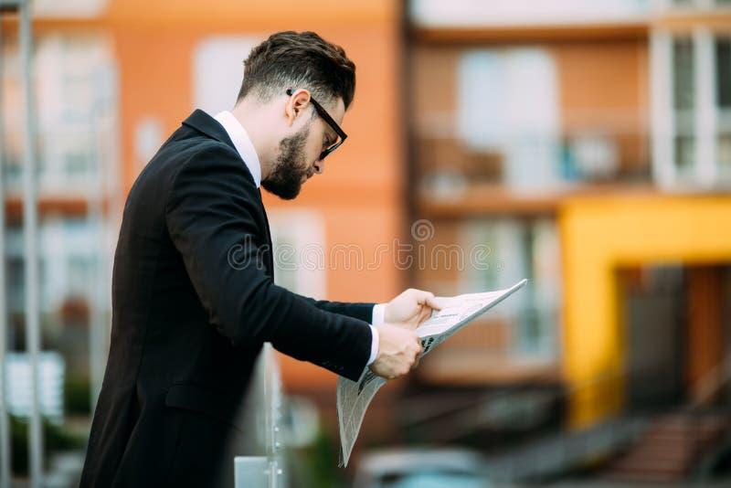 El hombre de negocios barbudo hermoso en traje clásico está leyendo un periódico y está sonriendo mientras que se coloca en el ba fotos de archivo