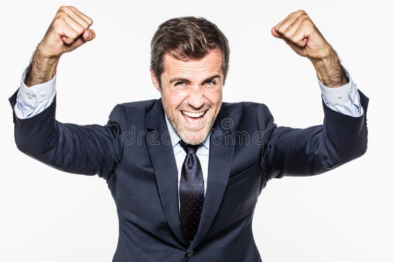 El hombre de negocios barbudo joven acertado con los brazos victoriosos aumentó la sonrisa imagen de archivo libre de regalías