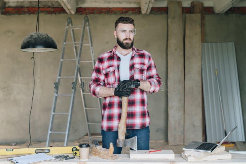 El hombre de negocios barbudo joven, constructor, reparador, carpintero, arquitecto, diseñador se vistió en camisa, gafas y guant fotos de archivo libres de regalías