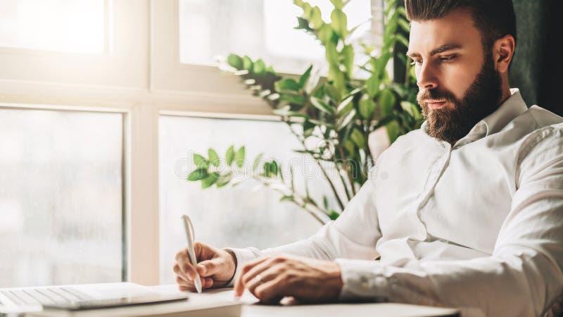 El hombre de negocios barbudo joven se está sentando en la tabla en oficina delante del ordenador portátil cerca de ventana y est imagen de archivo