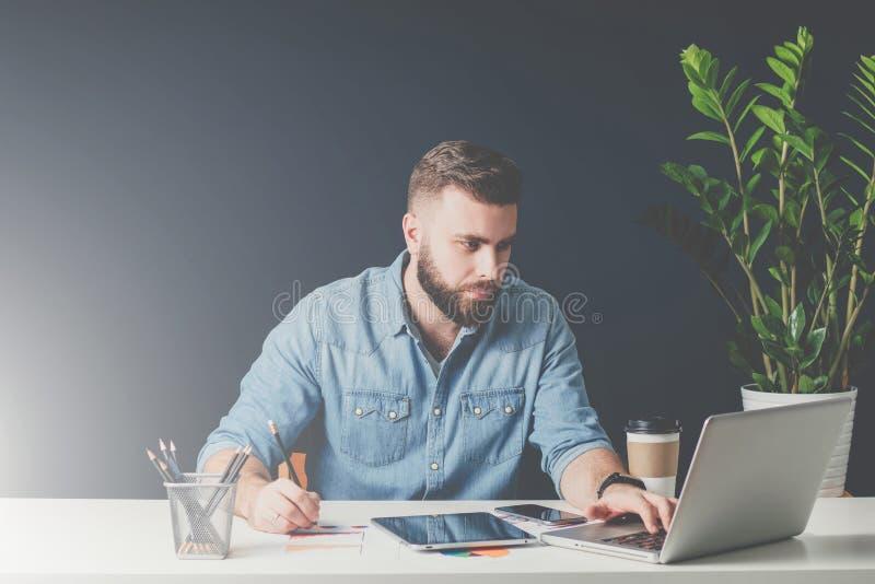 El hombre de negocios barbudo joven se está sentando en oficina en el escritorio, funcionamiento y está utilizando el ordenador p imagenes de archivo