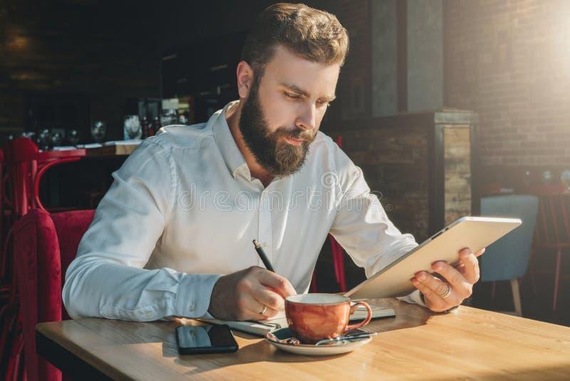 El hombre de negocios barbudo joven se sienta en el café, hogar en la tabla, tableta de las aplicaciones y escribe en cuaderno foto de archivo libre de regalías