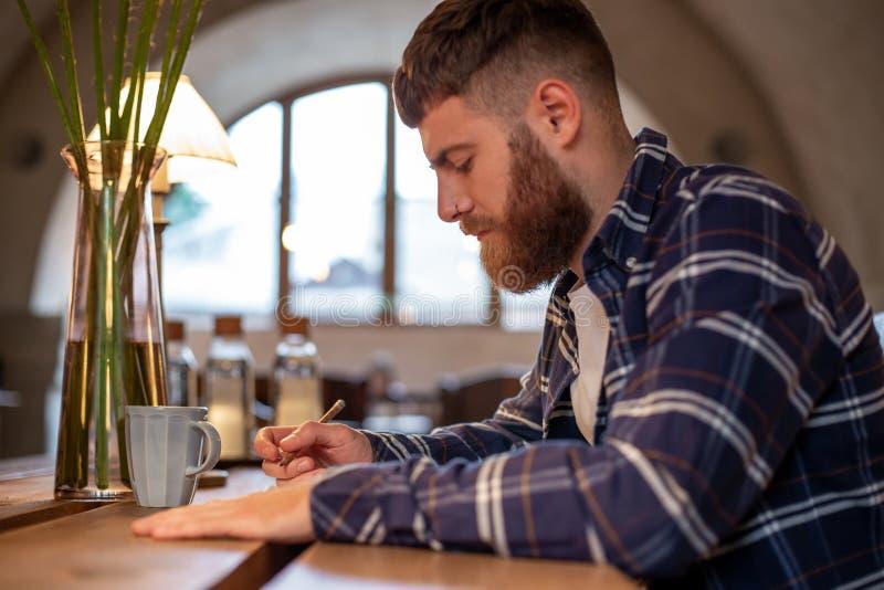 El hombre de negocios barbudo joven se sienta en el café, hogar en la tabla y escribe en cuaderno El hombre es trabajo, estudiand foto de archivo