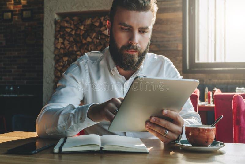 El hombre de negocios barbudo joven se sienta en oficina en la tabla, utiliza la tableta En el escritorio es el cuaderno, smartph foto de archivo