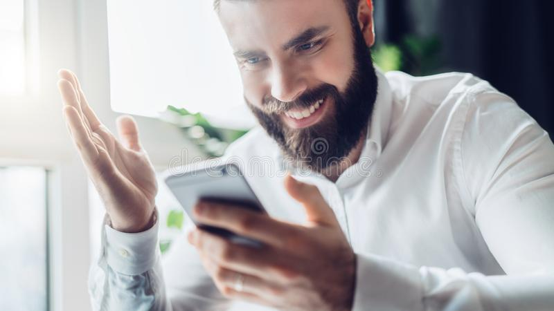El hombre de negocios barbudo se sienta en la tabla y mira feliz la pantalla del smartphone, aumentando su mano para arriba Buena fotografía de archivo libre de regalías