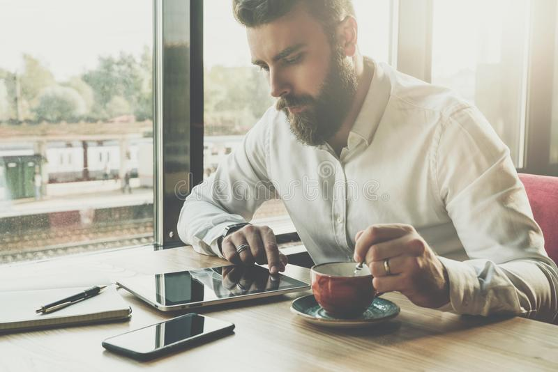 El hombre de negocios barbudo se sienta en oficina en la tabla, utiliza la tableta En el escritorio es el cuaderno, smartphone Fu foto de archivo libre de regalías
