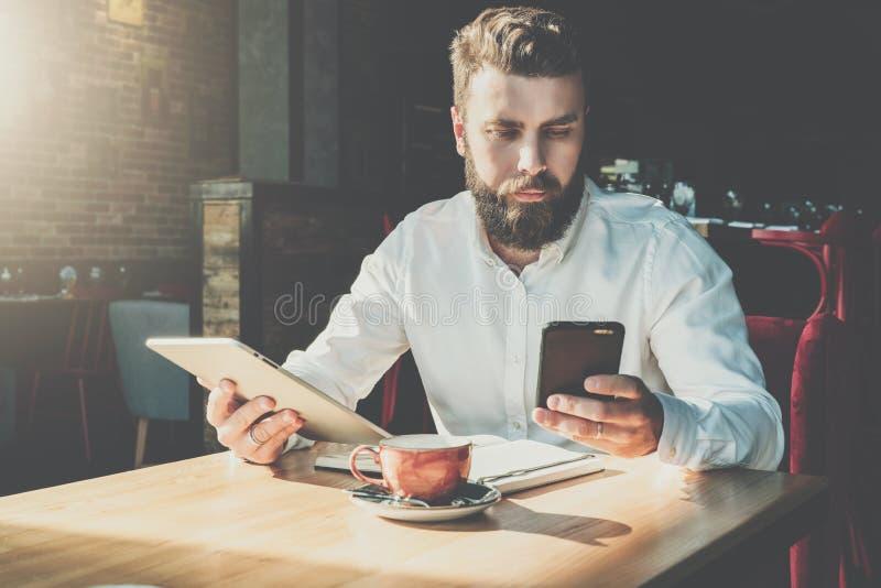 El hombre de negocios barbudo serio joven se sienta en café en la tabla, tableta digital de los controles, smartphone de las apli fotos de archivo libres de regalías