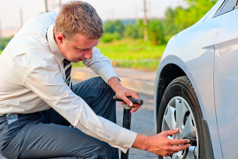 El hombre de negocios bombea la bomba del neumático de coche foto de archivo libre de regalías