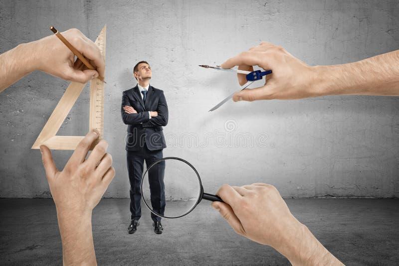 El hombre de negocios, brazos dobló, levantándose y mirando, y cuatro manos grandes alrededor de medirlo con la lupa imagen de archivo