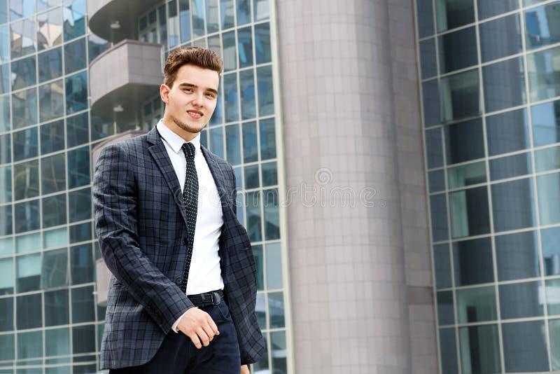 El hombre de negocios camina a lo largo del edificio de oficinas imagen de archivo