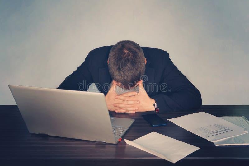 El hombre de negocios cansado agotado que trabaja en el ordenador portátil en la oficina, dando masajes a área temporal, sostenie fotos de archivo libres de regalías
