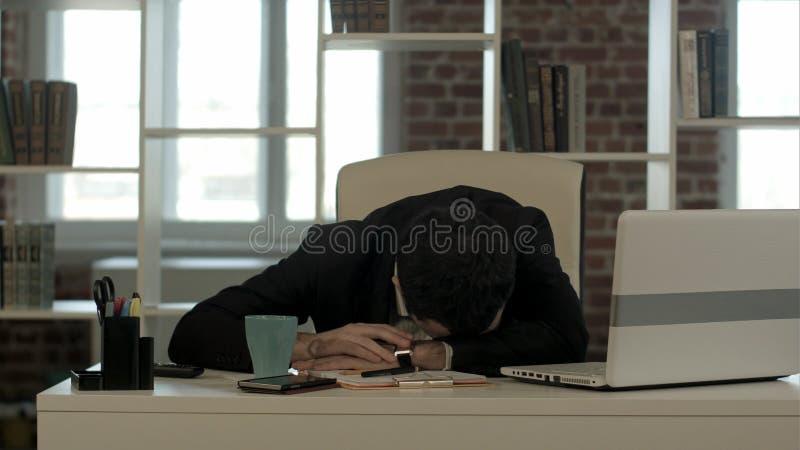 El hombre de negocios cansado que duerme con el ordenador portátil, despierta y comienza a hablar el teléfono foto de archivo libre de regalías