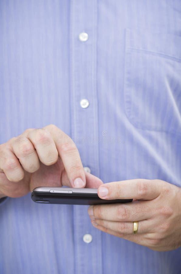 El hombre de negocios casual actúa un smartphone de la pantalla táctil imagen de archivo