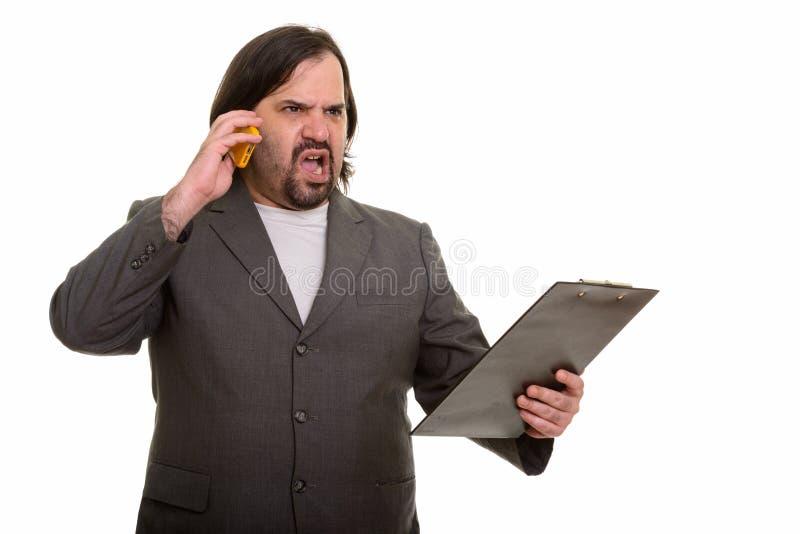 El hombre de negocios caucásico gordo enojado que habla en el teléfono móvil pasa ho fotos de archivo libres de regalías